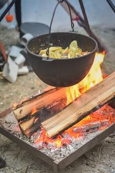 Kochen auf einem feuer in einem kessel, zubereitung von eintopf im kessel auf dem scheiterhaufen