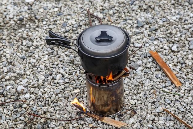 Kochen auf einem kleinen campingkocher in einem berglager.