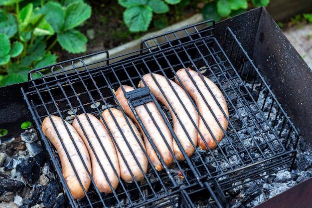 Kochen bayerischer würstchen auf einem grill im freien. picknick, essen im freien.
