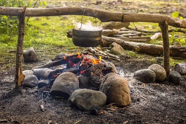 Kochen bei einer wanderung im kessel über dem feuer