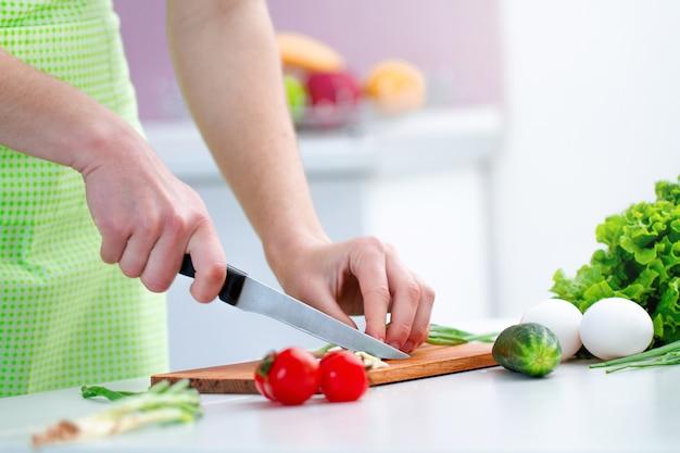 Kochen der person im schutzblech, das zu hause umweltfreundliche produkte für frischen gesunden gemüsesalat in der küche hackt.