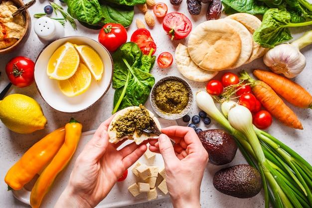 Kochen des gesunden vegetarischen lebensmittelhintergrundes. gemüse, pesto und früchte auf weißem hintergrund.