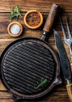 Kochen des hintergrundkonzeptes. vintagr eisen grillpfanne und besteck. ansicht von oben