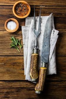 Kochen des hintergrundkonzeptes. weinlesetischbesteck, gewürze auf hölzernem hintergrund.