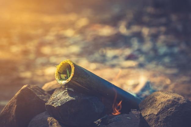 Kochen des lebensmittels im bambusrohr im wald