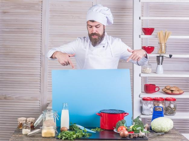 Kochen gut aussehender bärtiger koch in einheitlichen zutaten professioneller küchenchef hält werbung