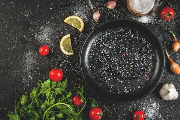 Kochen hintergrund zutaten und gewürze zum kochen abendessen: tomaten greens (petersilie) salz pfeffer zwiebeln schalotten knoblauch mit einer pfanne auf einem schwarzen betontisch