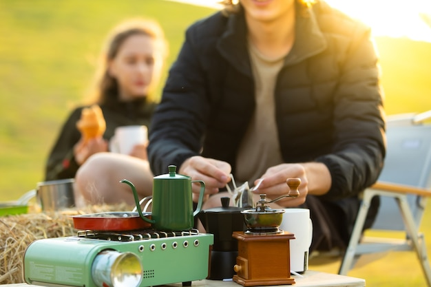 Kochen im freien auf dem campingplatz. junges kaukasisches paar, das morgens kaffee kocht und trinkt