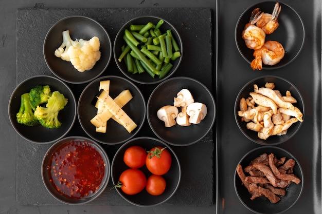 Kochen ingridients gemüse und fleisch in kleinen schalen auf schwarzem hintergrund