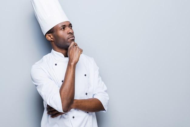 Kochen ist in meinem kopf. selbstbewusster junger afrikanischer koch in weißer uniform, der hand am kinn hält