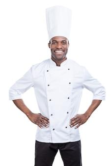 Kochen ist mein leben! selbstbewusster junger afrikanischer koch in weißer uniform, der die hände auf den hüften hält und lächelt