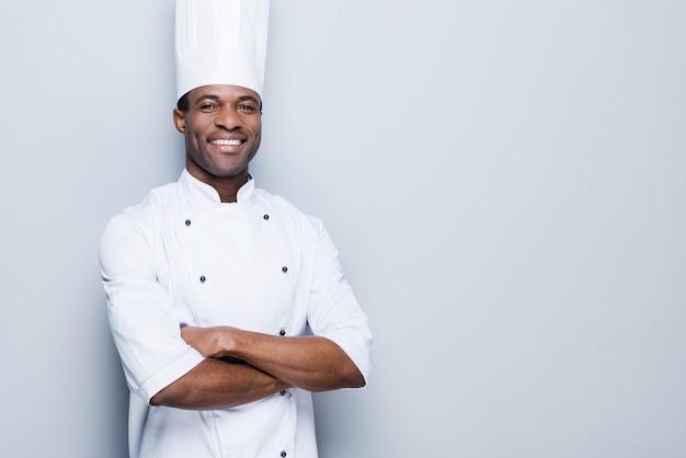 Kochen ist meine leidenschaft. selbstbewusster junger afrikanischer koch in weißer uniform mit verschränkten armen