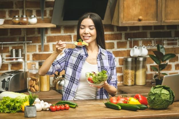Kochen junge frau in der küche mit löffel. versucht essen. lächelnd.