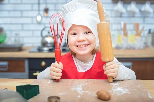Kochen macht spaß. kleines chefmädchen, das mit mehl spielt. junges mädchen, das an teig mit nudelholz arbeitet, um lebkuchenkekse zu machen.