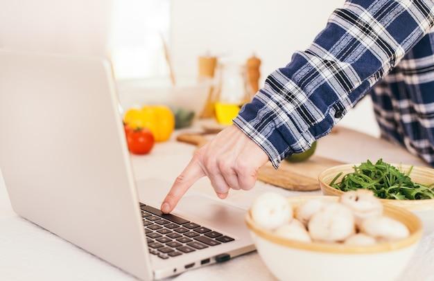 Kochen nach dem tutorial der virtuellen online-meisterklasse und betrachten des digitalen rezepts mit laptop-nahaufnahme