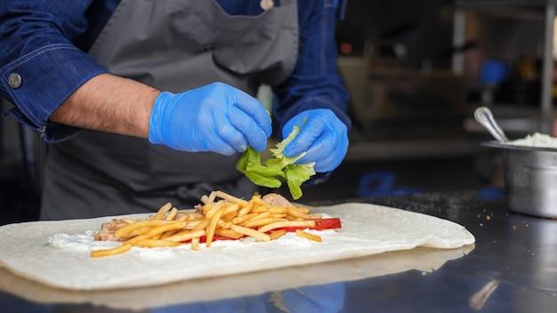 Kochen sie das hinzufügen von salat in einem wrap in einem food truck