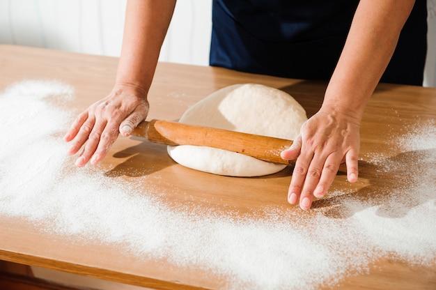 Kochen sie die hände, die teig kneten, stück teig mit weißem weizenmehl besprühen.