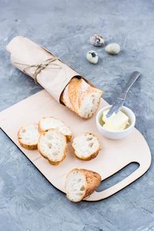 Kochen sie ein herzhaftes frühstück mit frischem baguette, butter und wachteleiern auf einem schneidebrett