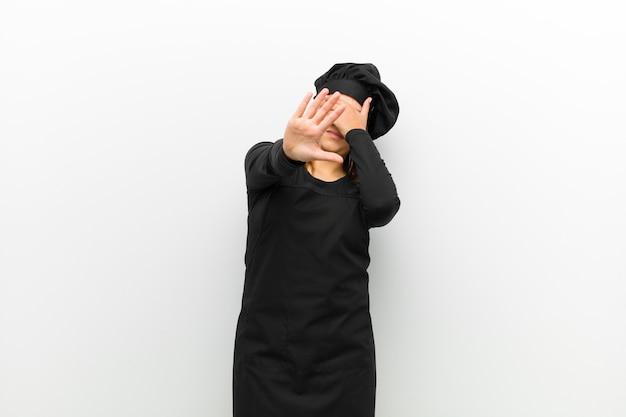 Kochen sie frauenbedeckungsgesicht mit der hand und setzen sie andere hand voran, um die kamera zu stoppen und fotos oder bilder gegen weiß ablehnen