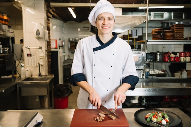 Kochen sie, gebratenes fleisch an bord nahe salat auf platte zu schneiden