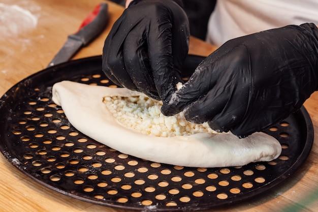 Kochen sie hände, die khachapuri in einem café nahe oben vorbereiten