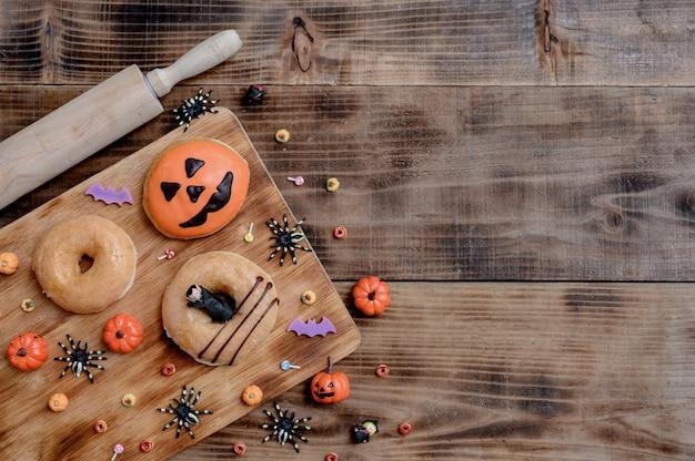 Kochen sie köstlichen hausgemachten kuchen und dekorieren sie donut für halloween festlich. süßes dessert und dekoration für die party zu hause.