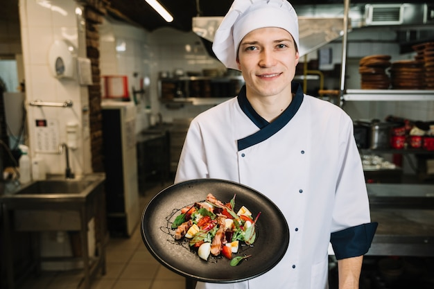 Kochen sie, salat mit fleisch auf platte zeigend