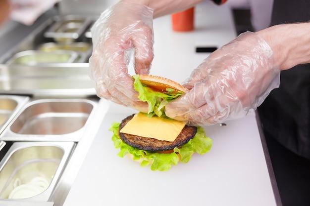Kochen sie und fügen sie eine zweite hälfte des burgers hinzu. burger im restaurant zubereiten. hände des kochs in einweghandschuhen entsprechend den hygieneanforderungen.