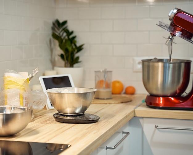 Kochen und backen küche zu hause, wohnung, mehl, waage, schalen, digitale tablette mit rezepten auf dem tisch