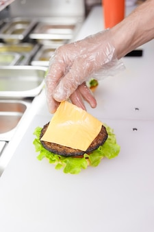Kochen und eine scheibe käse auf den burger geben. burger im restaurant zubereiten. hände des kochs in einweghandschuhen entsprechend den hygieneanforderungen.