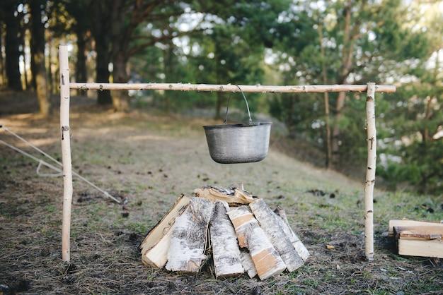 Kochen unter feldbedingungen, kochtopf am lagerfeuer beim picknick. gefiltertes bild: kreuzverarbeiteter vintage-effekt.