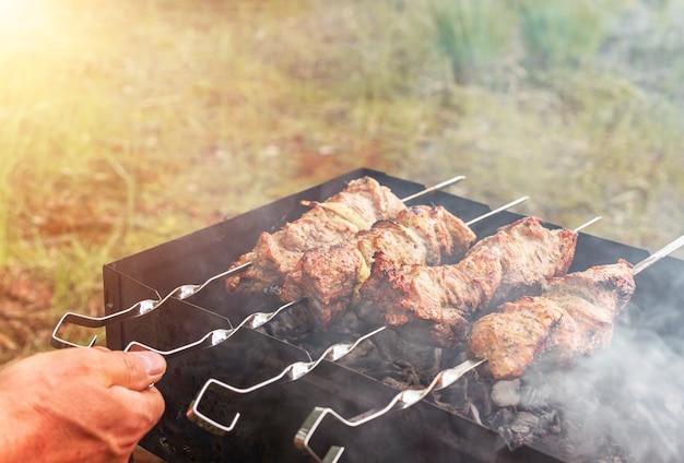 Kochen von fleisch auf kohlen für grillparty, nahaufnahme.
