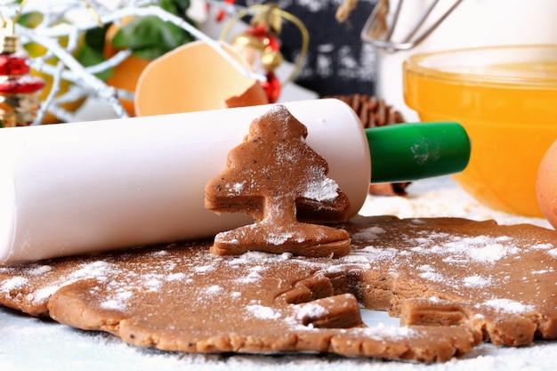 Kochen von ingwerplätzchen für weihnachtsselbst gemachte kuchen auf einer rustikalen art der hellen hölzernen hintergrundselektiven weichzeichnung