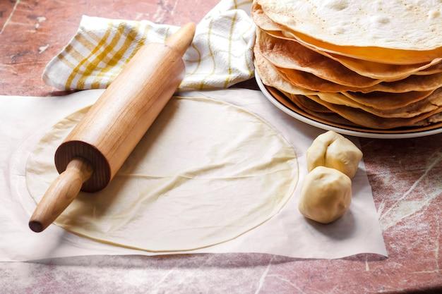 Kochen von kuchen napoleon - gebackene kuchenschichten, roher teig und nudelholz