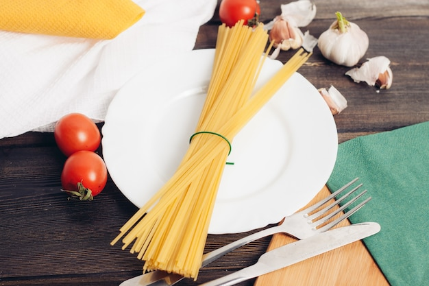 Kochen von nudeln mit tomaten küchentisch gabel und messer