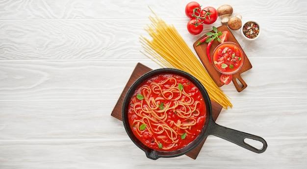 Kochen von spaghetti mit gekochter tomatensauce in einer gusseisernen pfanne, serviert mit chili-pfeffer, frischem basilikum, kirschtomaten und gewürzen über einem holztisch mit weißer textur, zutaten-lebensmittelkonzept