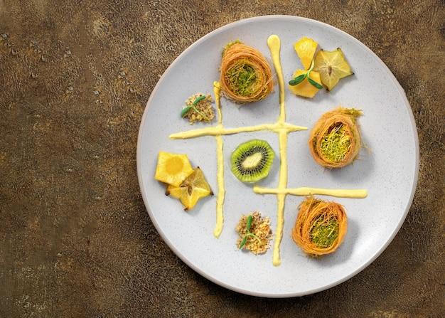 Kochen von süßigkeiten türkisches traditionelles ramadan-gebäckdessert kunafa (kadaif, baklava), kiwi, ananas, nüsse, dunkler hintergrund. plattenkunstkomposition.