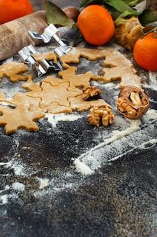 Kochen von weihnachtsplätzchen mit ausstechformen auf einem dunklen tisch