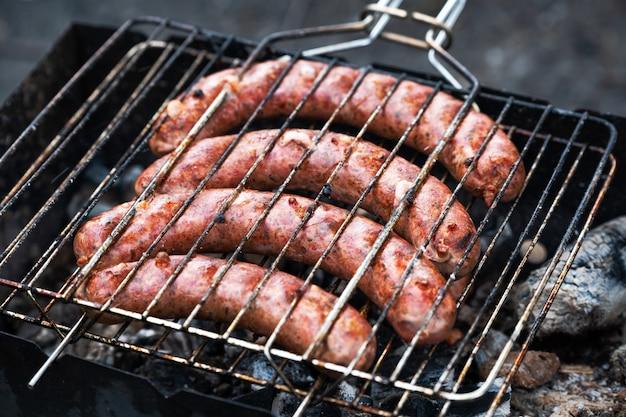 Kochen von würstchen auf dem grill beim grillen im freien bei einem picknick