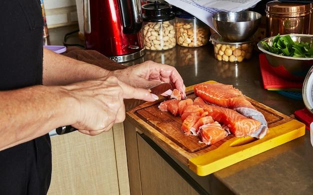 Kochen zu hause in der küche nach rezept aus dem internet. frau schneidet frischen lachs mit messer auf schneidebrett. schritt für schritt rezept.