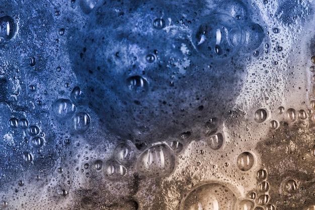Kochende dunkle flüssigkeit mit aquamarinschaum und großem klecks
