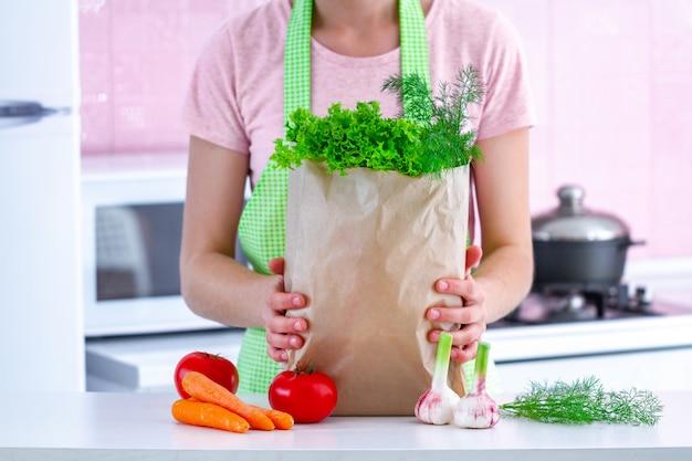 Kochende frau in der schürze, die eine handwerkliche papiertüte voll frisches bio-gemüse in der küche hält. gesunde ernährung und ausgewogene ernährung