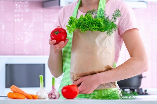Kochende frau in der schürze, die eine handwerkliche papiertüte voll frisches bio-gemüse in der küche hält. gesundes essen und ausgewogene ernährung, sauberes essen