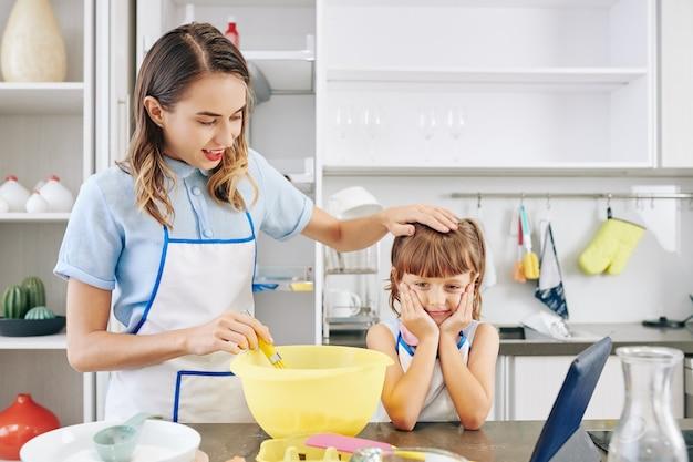 Kochende mutter streichelt den kopf der tochter und wartet darauf, dass der kuchen fertig ist