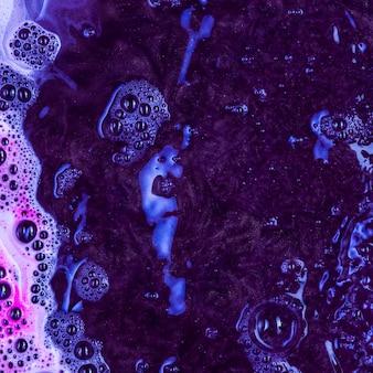 Kochende schwarze flüssigkeit mit blauem schaum