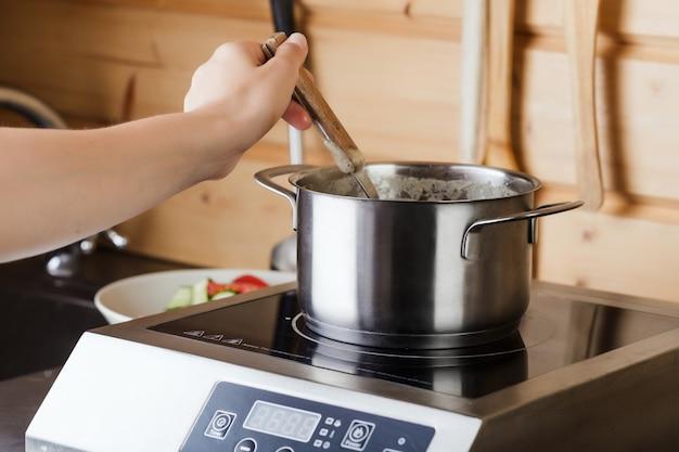 Kochende suppe in der wanne auf elektrischem ofen in der küche
