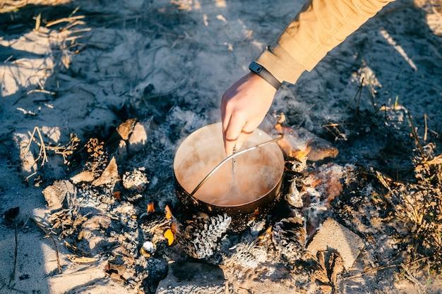 Kochender tee in der metallkanne im freien