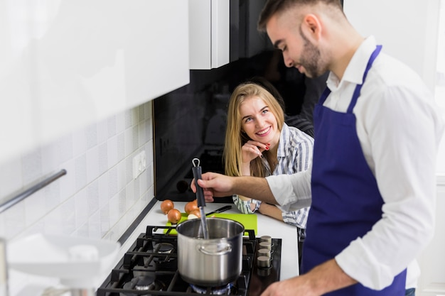 Kochendes wasser des mannes im topf auf ofen