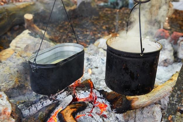 Kochendes wasser in zwei töpfen über dem feuer