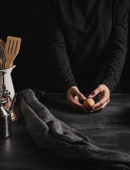 Kocher, der ei auf die küchenoberseite hält